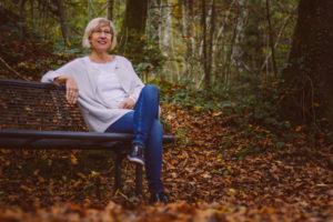 Sitzende Frau mit Jeans und Jacke im Wald auf einer Bank Seuzach Hettlingen