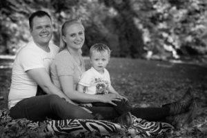 Sitzende Familie im Gras im Herbstwald aufgenommen in schwarz-weiss in Schaffhausen