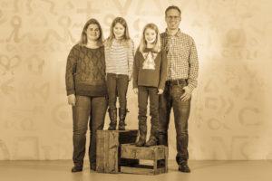 Eltern mit zwei Mädchen stehen nebeneinander für dein Familienfoto in Winterthur.