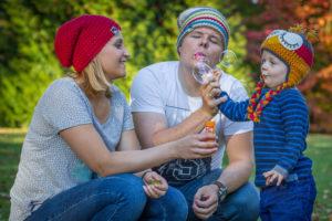 Seifenblasenspiel mit der kleinen Familie im Gras vor dem Herbstwald