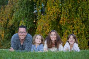 Familie liegt im Gras und lächelt in die Kamera des Fotografen und freut sich
