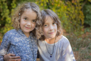 Zwei junge Geschwister umarmen sich und schauen gekonnt in die Kamera.