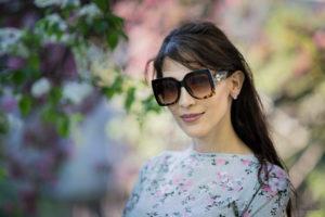 Junge Frau mit Sonnenbrille portraitiert vor einer Blütenpracht.