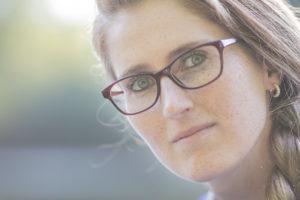 Das Portrait einer jungen Frau mit roter Brille und zu einem Zopf gebundenen Haaren.