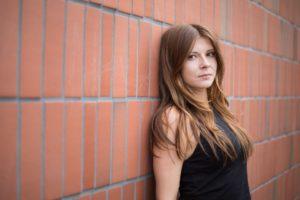 Bild von einer Frau fotografiert die an eine Backsteinwand anlehnt und die Haare offen trägt