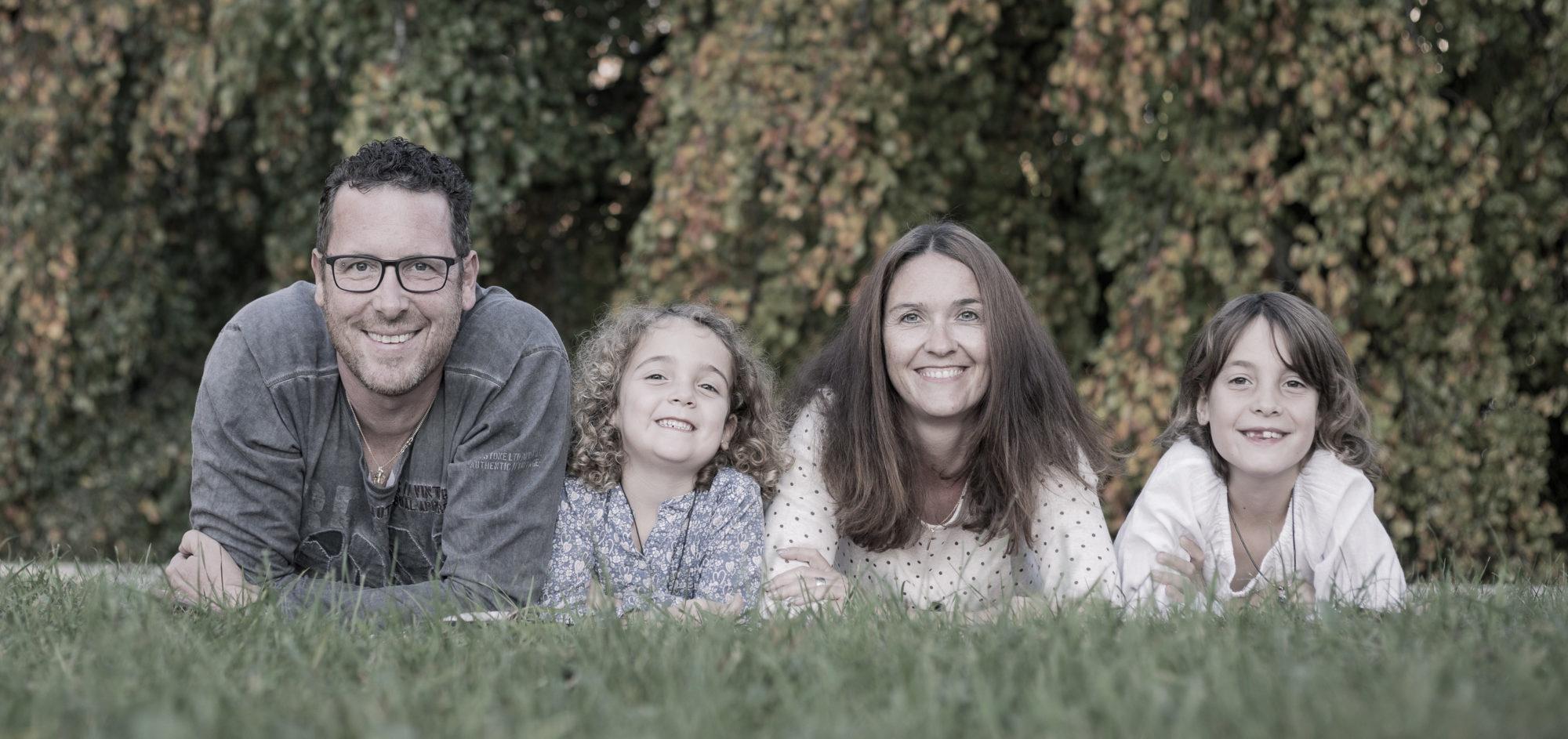 Der Fotograf hat hier eine Familie fotografiert, welche im Gras liegt