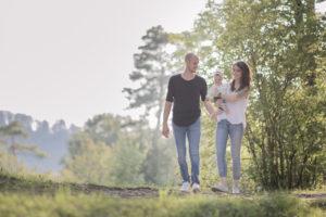 Die Eltern spazieren draussen mit ihrer Tochter auf dem Arm.