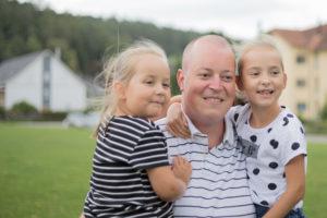 Vater wurde fotografiert als er seine zwei kleinen Töchtern auf dem Arm hat.