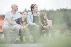 Eine junge Familie mit zwei Kindern sitzt draussen auf einer Holzbank.