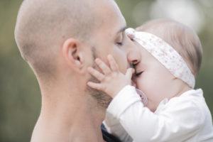 Vater küsst seine kleine Tochter mit geschlossenen Augen