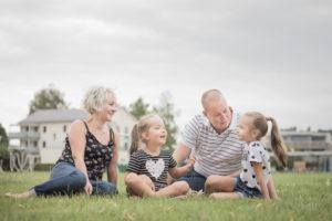 Familie sitzt im Gras und redet miteinander. Eltern mit zwei kleinen Mädchen.
