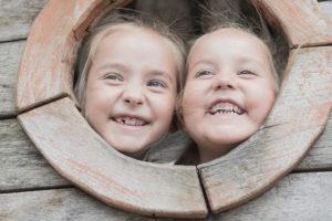 Zwei kleine Mädchen schauen lachend aus einem runden Loch heraus.