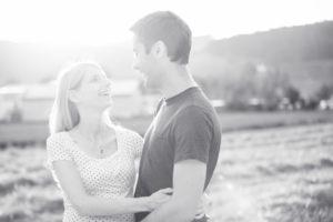 Schwarz-Weiss Foto der zukünftigen Eltern welche sich umarmen.