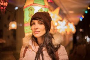 Model mit Mütze fotografiert vor einem Restaurant mit farbigen Lichtern in Zürich