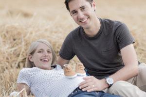 Die werdende Mutter liegt im Stoppelfeld und ihr Mann sitzt daneben. Auf ihrem Bauch sind zwei Babyschuhe. Er hält seine Hand auf ihren Bauch.